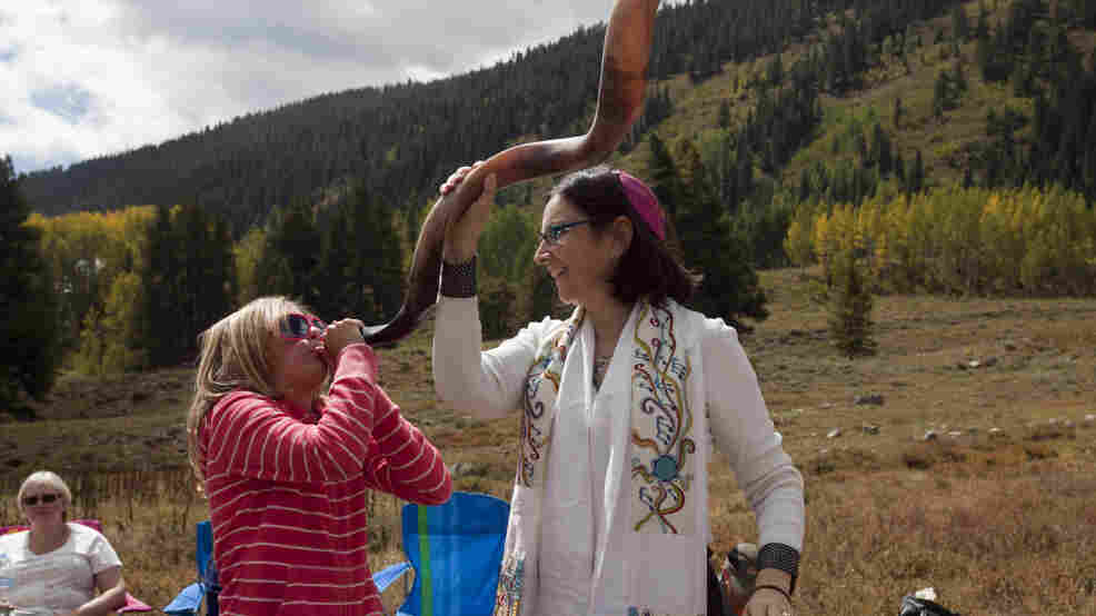 A 10-year-old girl blows a shofar with the help of Cantor Robbi Sherwin during Rosh Hashana services in the mountains of Crested Butte, Colo., last year. Rosh Hashana marks the beginning of the Jewish new year.
