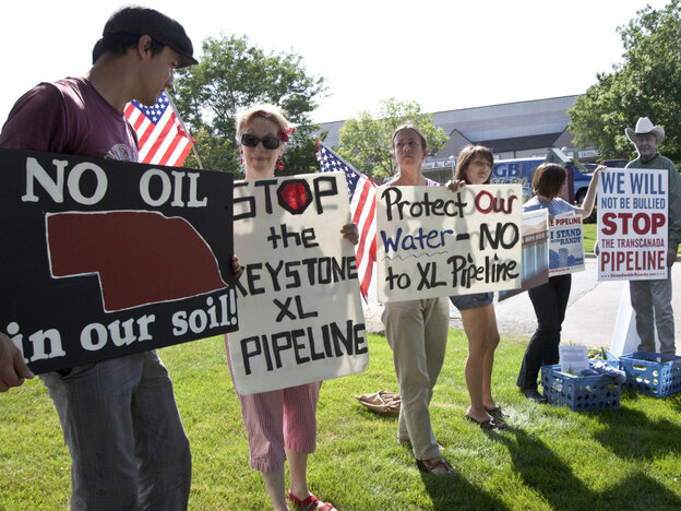 Protestors opposed to the Keystone XL pipeline hold signs outside the office of Rep. Lee Terry, R-Neb., in Omaha, Neb., Tuesday, July 26, 2011.