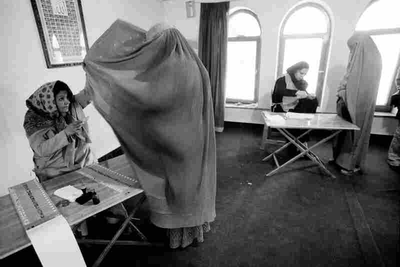 An election worker checks the identity of a voter at a polling station during Afghanistan's presidential election, Kabul, 2004.