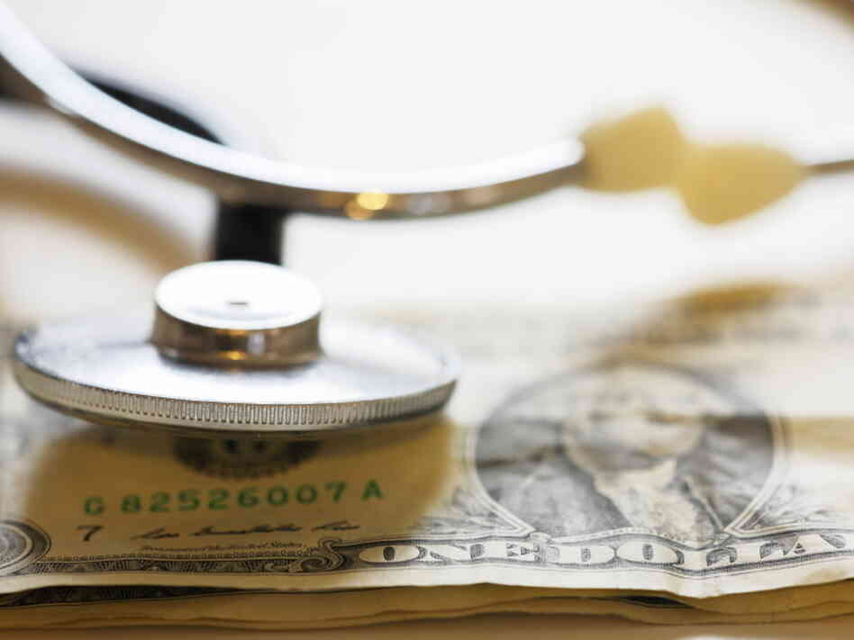 A stethoscope rests on a dollar bill.