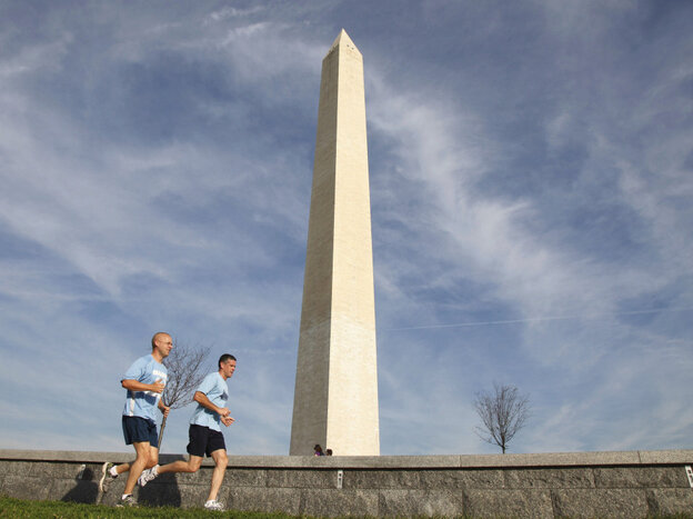 Joggers run past the Washington Monument in Washington, Wednesday, Aug. 24, 2011, which remains closed after Tuesday's earthquake.