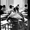 An unidentified African American student sits inside a classroom at Clinton High School, which was newly integrated when this photo was taken on Aug. 31, 1956. She sits in a rear seat near the door and is separated by empty desks as the white children sit at the far side of the room.