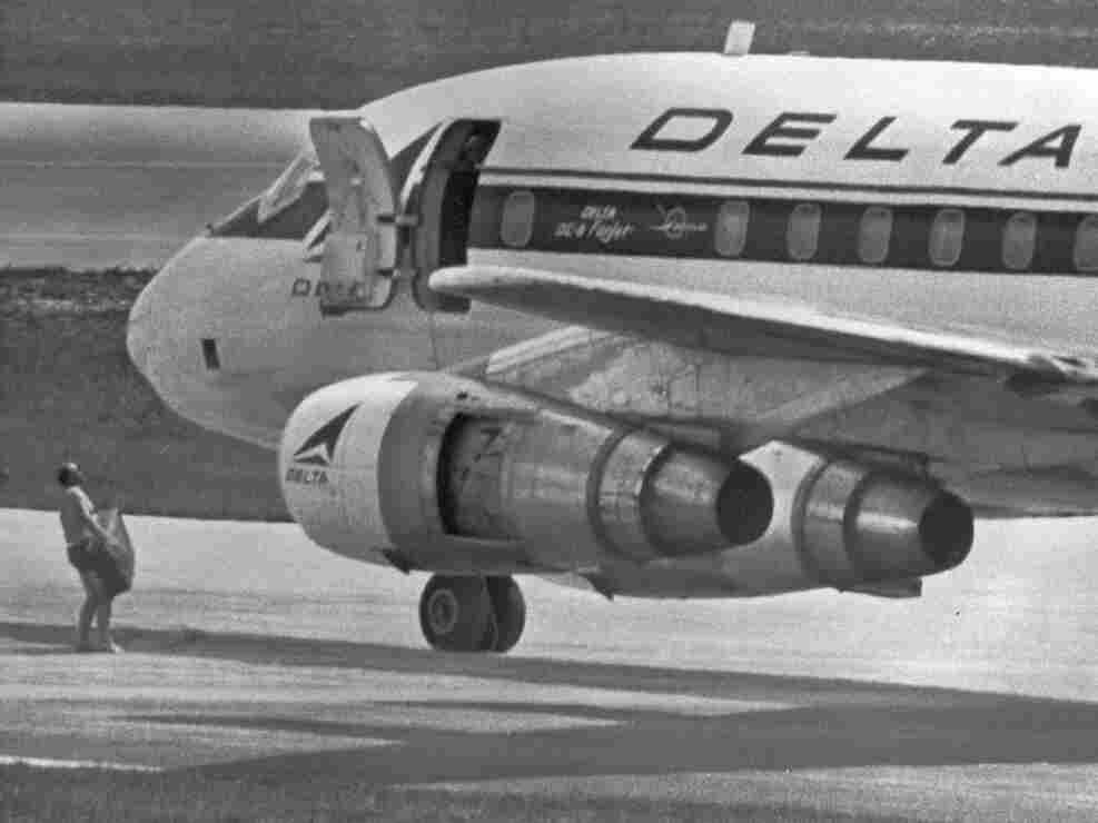 July 1972: an FBI agent, wearing only a pair of swim trunks, per the hijackers' instructions, carries a case containing a $1 million ransom to the opened door of a hijacked Delta DC8 jet in Miami. The jet later took off for Algeria. George Wright, a convicted killer and 1970s militant, was among the hijackers.