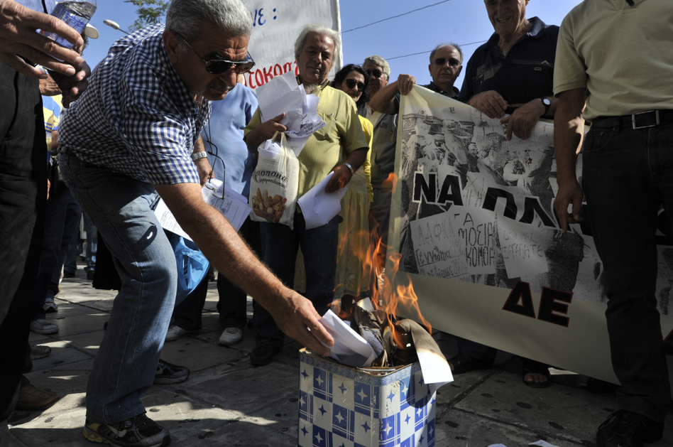 A Greek pensioner burns his emergency tax bill during a protest Wednesday outside the Ministry of Finance in the center of Athens.