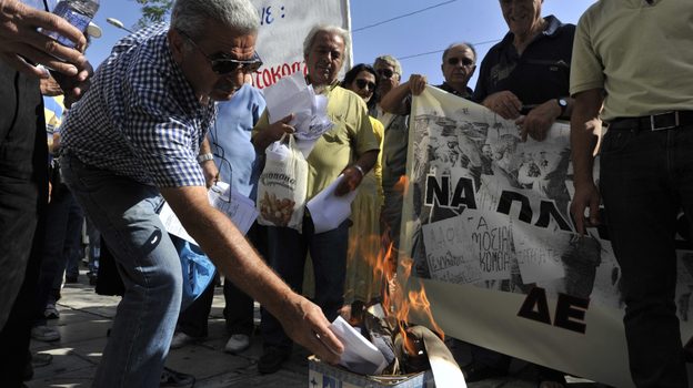 A Greek pensioner burns his emergency tax bill during a protest Wednesday outside the Ministry of Finance in the center of Athens. (AFP/Getty Images)