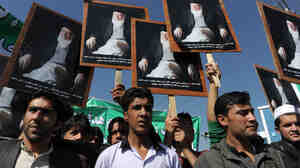 Afghans hold portraits of former President Burhanuddin Rabbani,  as they shout anti-government slogans  during a demonstration in Kabul on Tuesday. Last week's killing of Rabbani, an ethnic Tajik, was the latest targeting his party and it has stoked fears of increased factionalism.