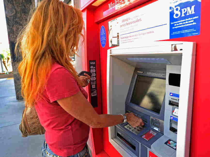 A customer uses a Bank of America ATM in Los Angeles. The bank plans to start charging a $5 monthly fee for customers who use their debit card for purchases starting early in 2012. ATM transactions would still be free.