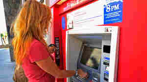 A customer uses a Bank of America ATM in Los Angeles. The bank plans to start charging a $5 monthly fee for customers who use their debit card for purchases starting early in