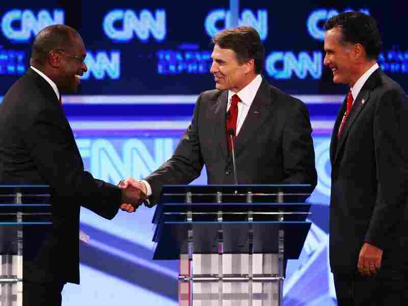 Republican presidential candidates Herman Cain, Gov. Rick Perry  and Mitt Romney at the presidential debate sponsored by CNN  and The Tea Party Express at the Florida State fairgrounds on Sept.  12, 2011 in Tampa, Florida. The debate featured the eight candidates ten  days before the Florida straw poll.