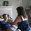 """Laura Zakhar connects her son, Kevin, 15, to the """"feedbag"""" that contains his nutrition. Lately, Zakhar has had trouble getting the calcium solution Kevin needs, in part because  hospitals have been reserving limited supplies for patients who need it even more desperately  than he does."""