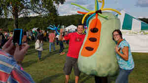Fans pose for a picture with a pawpaw character at the 13th Annual Pawpaw Festival in Albany, OH.
