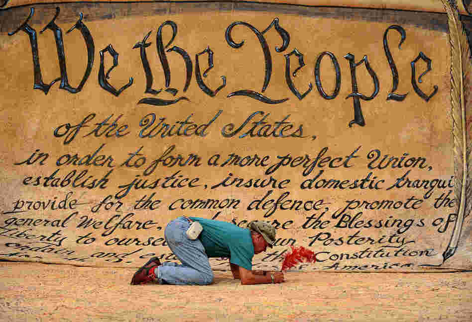 A man signs a huge banner depicting the Preamble to the Constitution during an Occupy DC anti-corporations protest at Freedom Plaza in Washington, D.C.