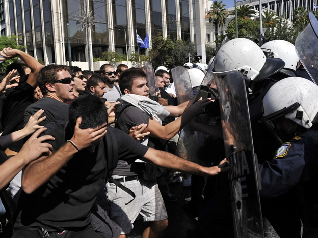 <p>High school students protesting austerity measures clash with riot police in front of the Greek Parliament on Monday. Also Monday, the Greek government announced that it would not meet its targets for reducing the budget deficit.</p>