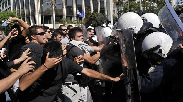 High school students protesting austerity measures clash with riot police in front of the Greek Parliament on Monday. Also Monday, the Greek government announced that it would not meet its targets for reducing the budget deficit. (AFP/Getty Images)