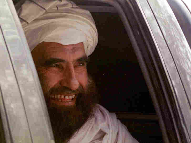 """In this archive photo from October 21, 2001, Jalaluddin Haqqani smiles as he leaves after a meeting with Jama""""at-i-Islami leaders in Islamabad, Pakistan."""
