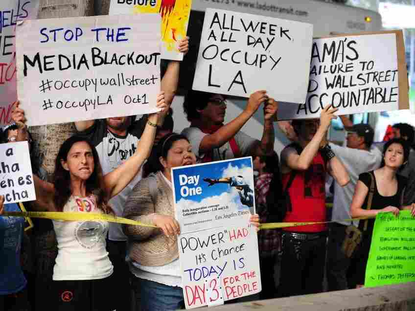 Protesters shout slogans while holding banners Monday at  Occupy Wall Street protests in Los Angeles.