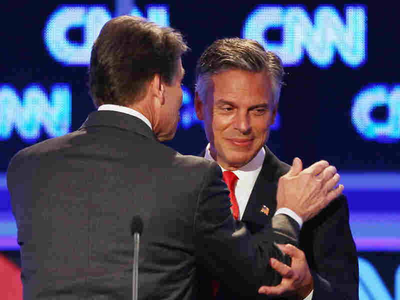 """Former Utah Gov. Jon Huntsman (right) and Texas Gov. Rick Perry confer during a break in the Sept. 12 presidential debate in Tampa. Huntsman first objected to Perry's use of the word """"treasonous"""" then later used it himself."""