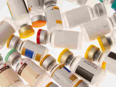 Vials of different vaccines with color-coded caps.
