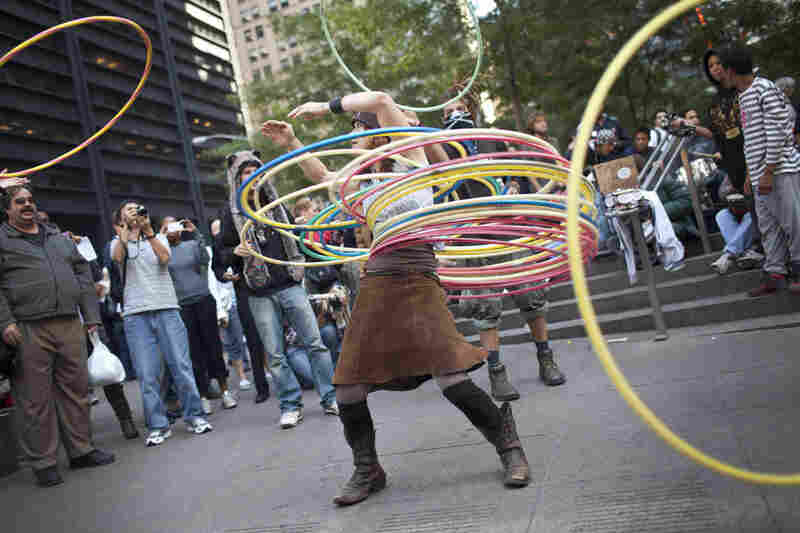 "A woman who identified herself as ""Marygoround"" attempts to balance numerous hula hoops while others toss more at her during the Occupy Wall Street protests in Zuccotti Park, New York, in early October."