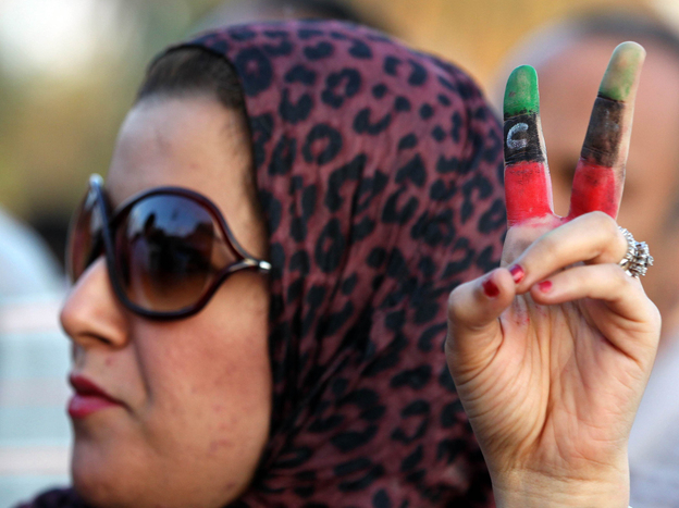<p>A woman flashes the victory sign with the colors of Libya's new flag on her fingers as demonstrators rally in support of the Transitional National Council in Tripoli on Monday. Women are seeking an expanded role following Libya's revolution.</p>