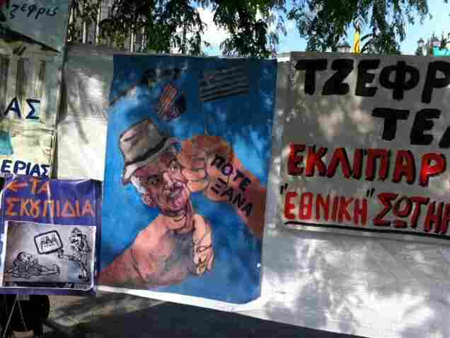 """A poster depicts Greek Prime Minister George Papandreou as an American puppet. The words on the hand hitting Papandreou's face are """"never again""""."""