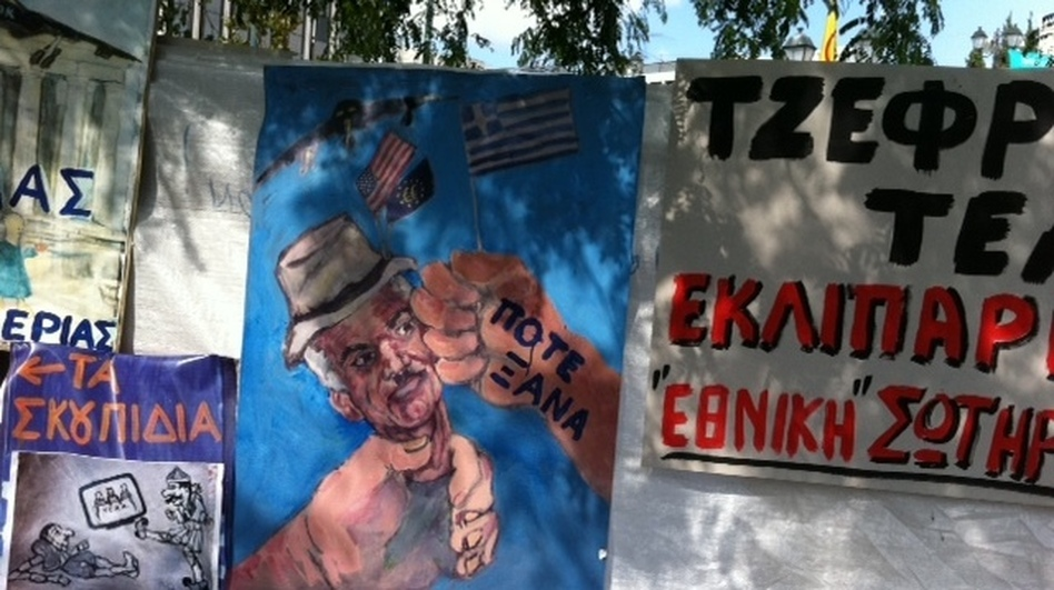 """<p>A poster depicts Greek Prime Minister George Papandreou as an American puppet. The words on the hand hitting Papandreou's face are """"never again"""".</p>"""