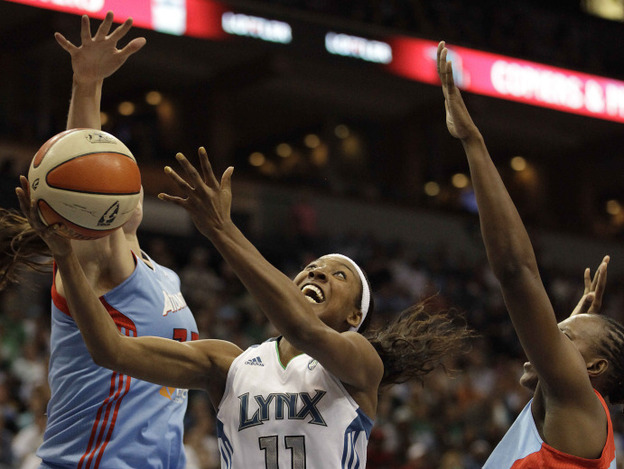<p>Minnesota Lynx guard Candice Wiggins (center) goes up for a shot against Atlanta Dream center Alison Bales (left) and forward Sancho Lyttle in the second half of Game 1 of the WNBA finals basketball series on Sunday.</p>