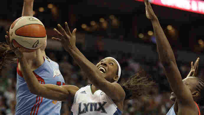 Minnesota Lynx guard Candice Wiggins (center) goes up for a shot against Atlanta Dream center Alison Bales (left) and forward Sancho Lyttle in the second half of Game 1 of the WNBA finals basketball series on Sunday.