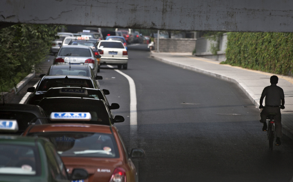 <p>A cyclist in passes a line of cars during rush hour in Beijing. While auto sales remain strong in China, the country is also reportedly experiencing a resurgence of interest in bicycles.</p>