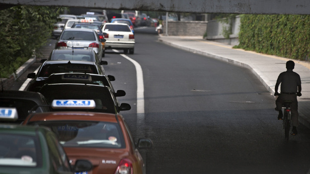 A cyclist in passes a line of cars during rush hour in Beijing. While auto sales remain strong in China, the country is also reportedly experiencing a resurgence of interest in bicycles. (AP)
