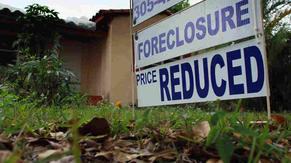 A foreclosure/price reduced sign stands in front of a home for sale on February 11, 2011 in Miami.
