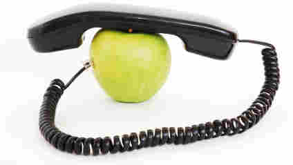 An apple with a phone handset on top of it.