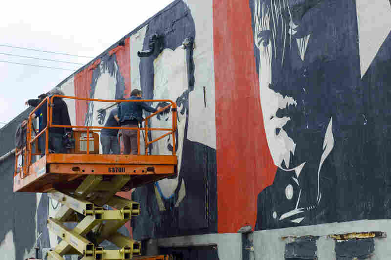Touching up the rock-star mural outside Asbury Lanes.