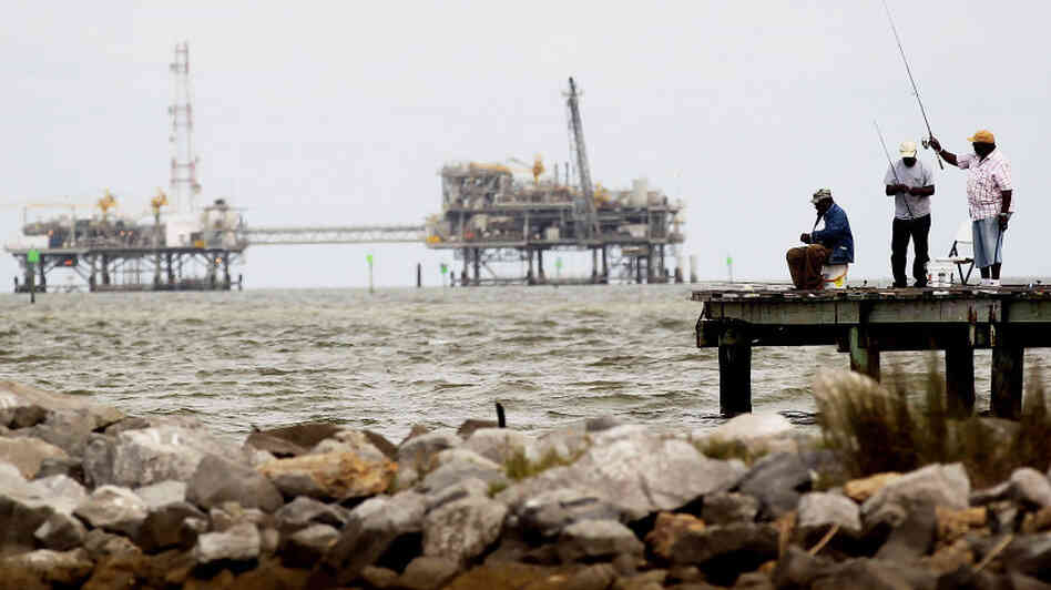 Men fish off a pier at a jetty in Dauphin Island, Ala., with oil rigs in the background. The U.S. government is changing how it regulates drilling platforms.