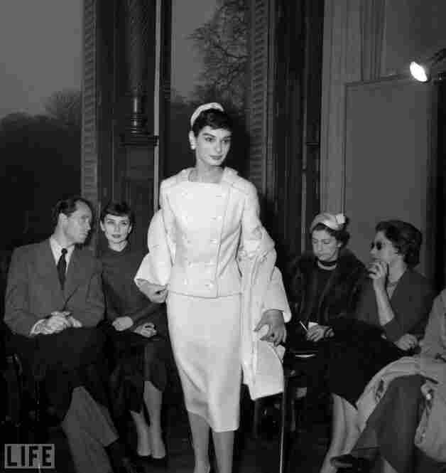 Hepburn (left) sits with her then-husband Mel Ferrer at a 1955 Givenchy show in Paris.
