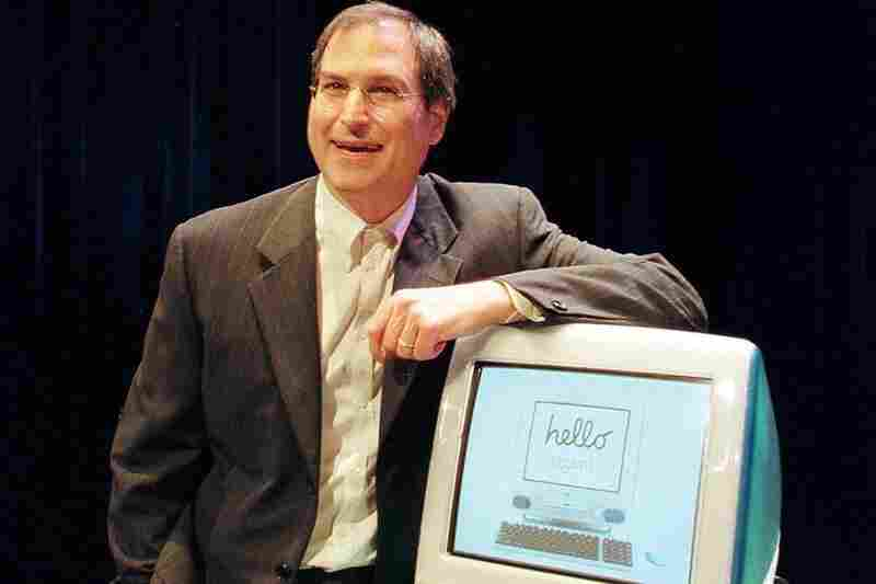 Jobs poses with the first iMac in 1998.