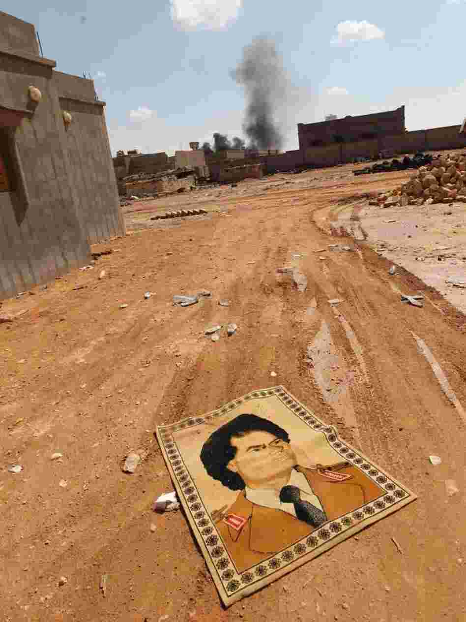 A small carpet with the portrait of Gadhafi lies on the ground near fighting at the front line of Bani Walid, southeast of Tripoli, earlier this month.