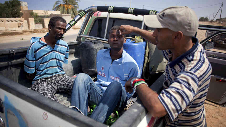 A revolutionary fighter watches over two suspected Gadhafi loyalists in Sirte, Libya, last month. By some estimates, up to 30 to 40 percent of Libyans are sympathetic to former dictator Moammar Gadhafi.