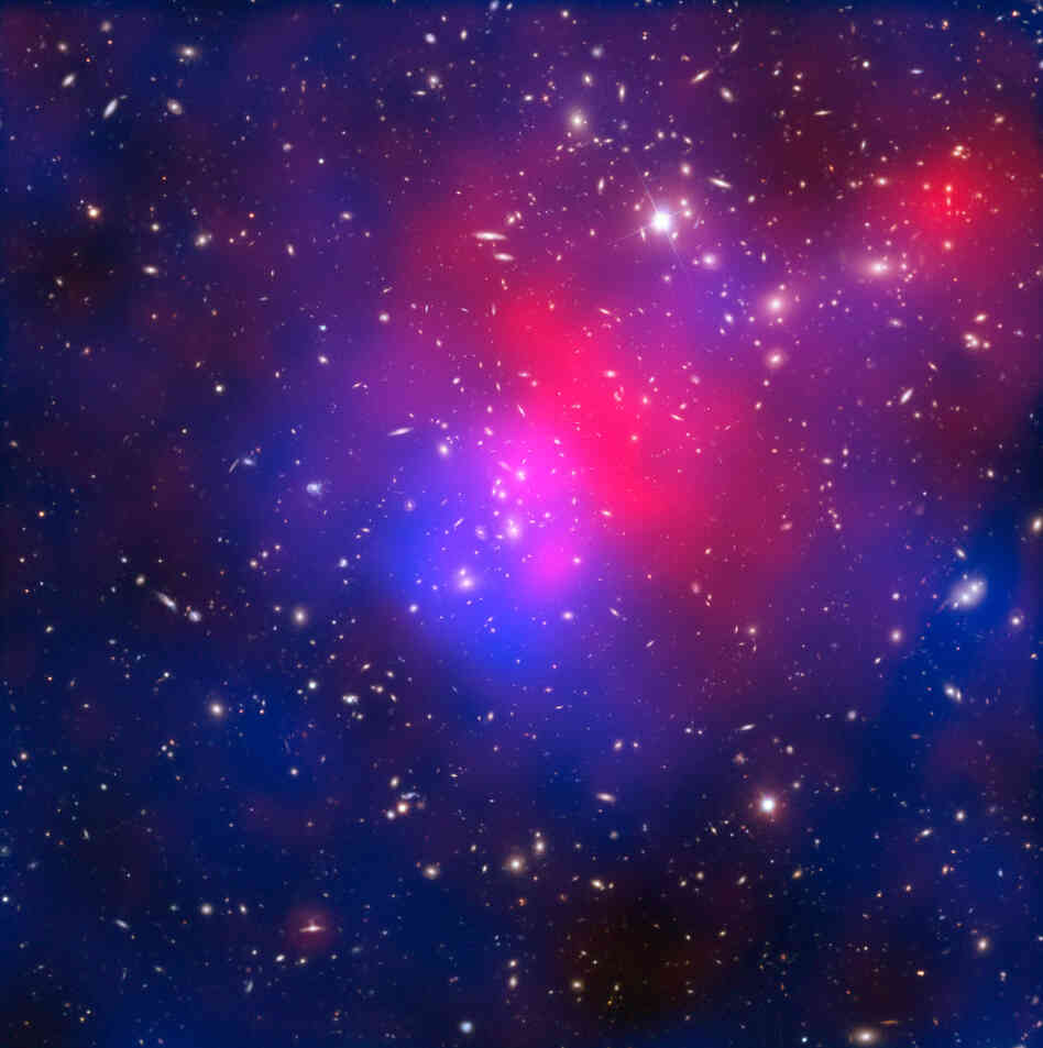 This image combines visible light exposures of galaxy cluster Abell 2744 taken by the NASA/ESA Hubble Space Telescope and the European Southern Observatory's Very Large Telescope, with X-ray data from NASA's Chandra X-ray Observatory and a mathematical reconstruction of the location of dark matter.