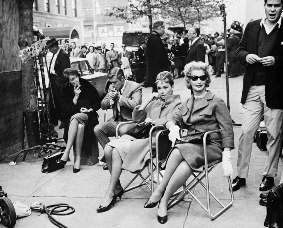 Actors, including Audrey Hepburn, take a break during location filming for Breakfast At Tiffany's in 1961.