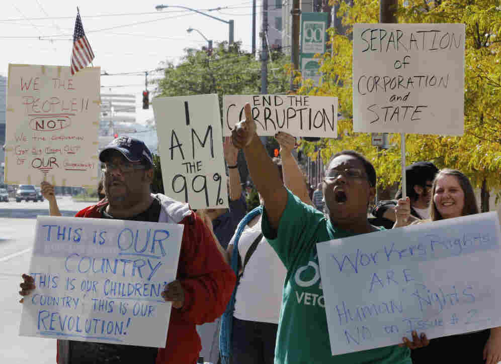 Protesters organized by Occupy Wall Street and Occupy Together yell slogans and hold signs at Courthouse Square in Dayton, Ohio, Wednesday. Several large unions have come out in support of Occupy Wall Street.