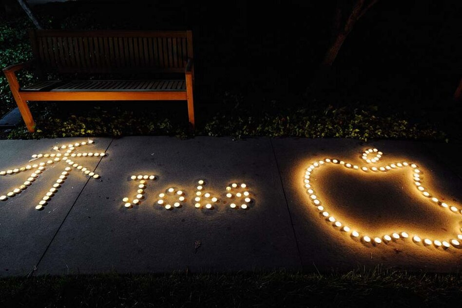 Chinese exchange students from nearby De Anza College use candles to create a makeshift memorial for Steve Jobs at the Apple headquarters.  (Getty Images)