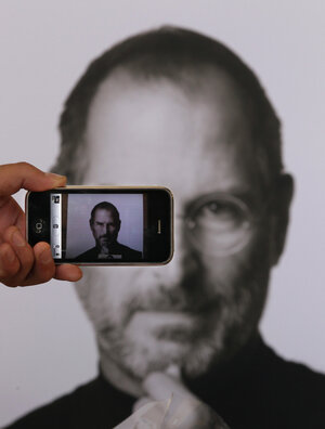 A photographer uses his iPhone to take a picture of a tribute to Apple co-founder Steve Jobs i