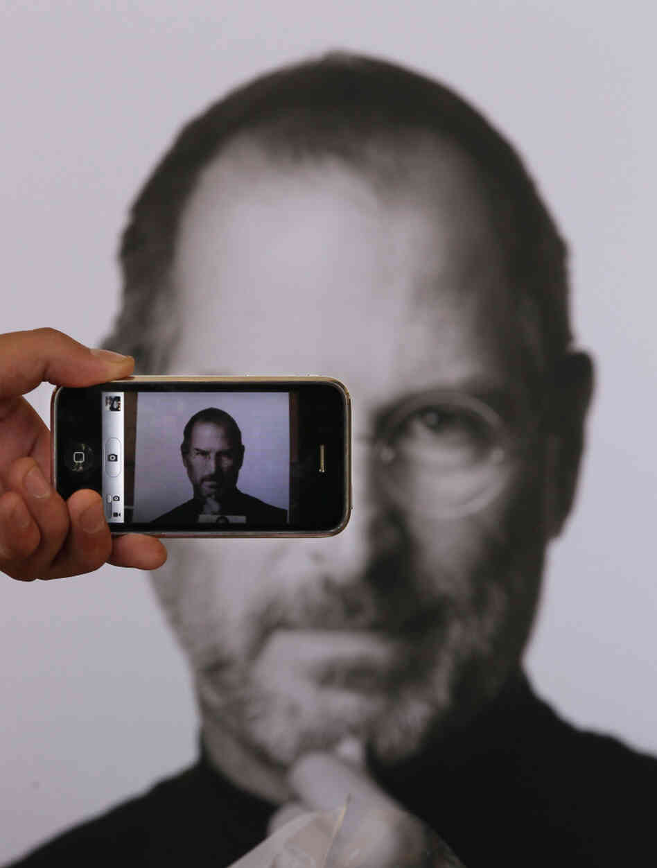 A photographer uses his iPhone to take a picture of a tribute to Apple co-founder Steve Jobs in front of an Apple store in London. Jobs, 56, died Wednesday after a long battle with pancreatic cancer.