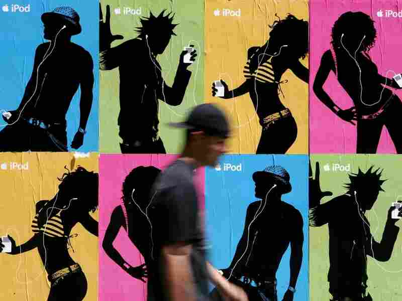 A pedestrian passes a wall covered with Apple iPod advertisements July 14, 2005 in San Francisco.