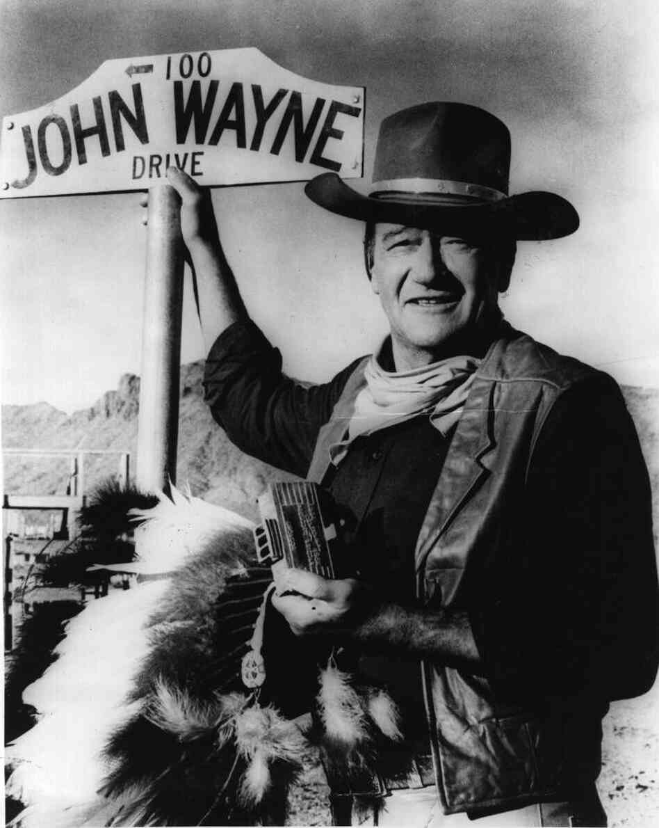 "American actor John Wayne stands by the street sign honoring his name in Prescott, Ariz. The film star ""was one of the defining Americans of the 20th century,"" says critic John Powers."