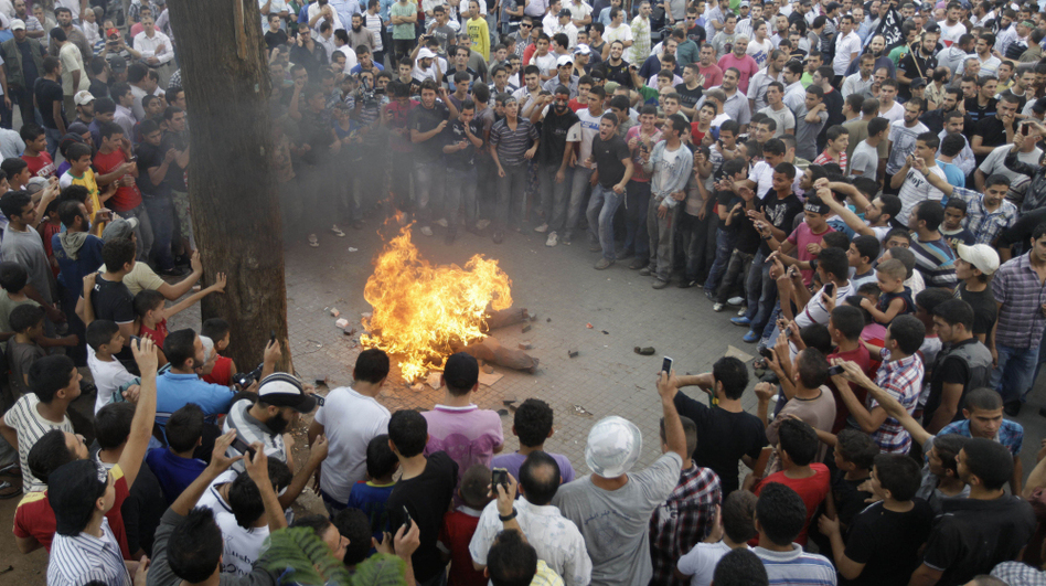 <p>Protesters opposed to Syrian President Bashar Assad burn an effigy of him during Friday prayers in Tripoli, Lebanon.</p>