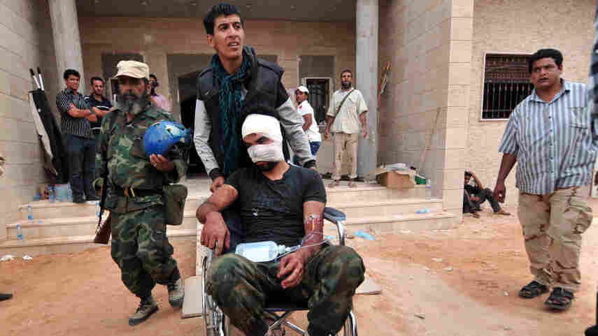 On a morning of fierce street fighting, a wounded man is wheeled into a field hospital outside Sirte. The city was rocked by explosions, and Libyan National Transitional Council fighters were targeted by pro-Gadhafi snipers.