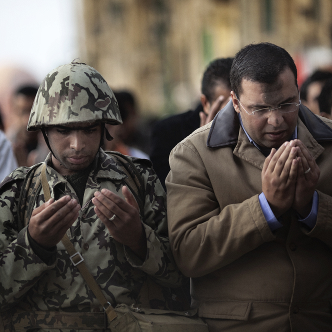 Jan. 30, 2011: In Cairo's Tahrir Square, an Egyptian army soldier joins a crowd of Muslim demonstrators to say prayers.