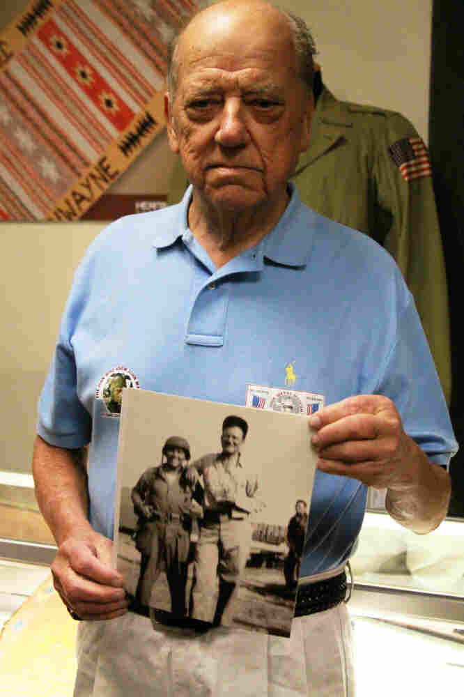 Bill Atkins, 80, holds a blurry photo of himself at age 19 with John Wayne during the filming of Flying Leathernecks. Atkins came from Bowie, Md., to view the auction.